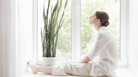 Woman sitting on windowsill with flower meditating