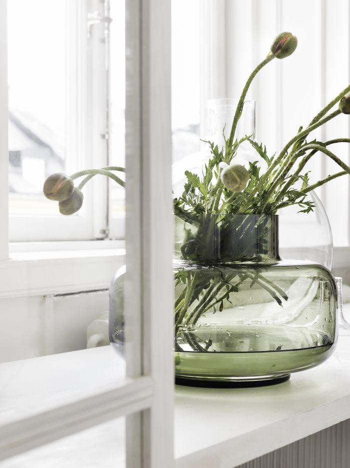 flowers in green vase by window