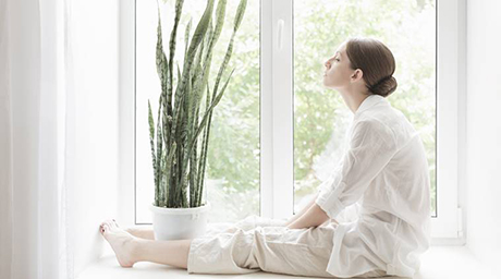 woman sitting on windowsill with flower meditating
