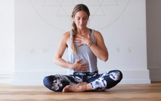 woman meditates hand on heart